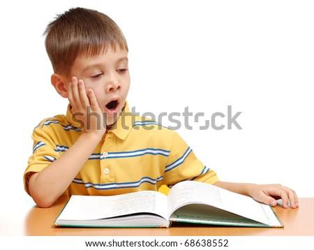 Boy reading book and yawning isolated on white background