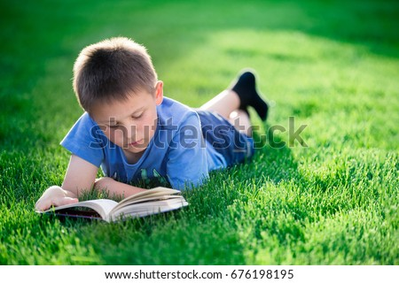 Boy reading book, lying down on green grass