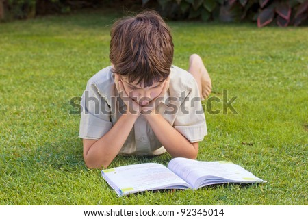 boy  reading book on green grass lawn