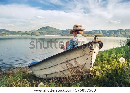 Boy reading in old boat on the lake bank #376899580
