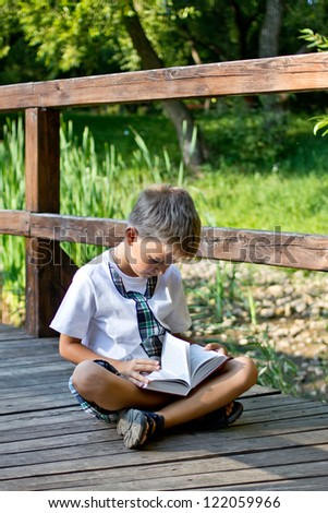 Boy Reading, sitting on the bridge against canes