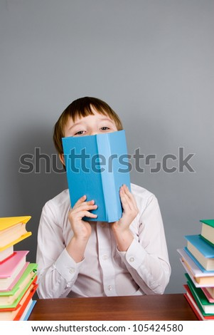 Boy reads a book on a gray background