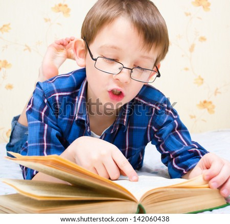 boy reads the book indoors