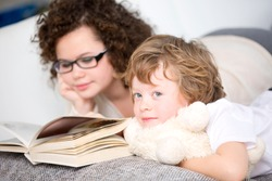 Boy relaxing on sofa with sister reading book
