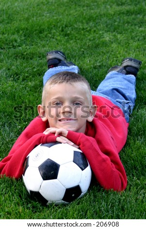 Boy resting on a soccer  ball.