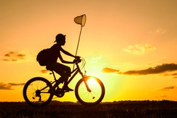 Boy returning from a trip in the evening with butterfly net and rucksack, silhouette of child riding bicycle in nature
