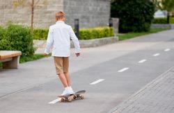 Boy Ride Skateboard in City Street. Young Teenager on Skate in Park. Urban Summer Lifestyle. Teen Skater Drive Longboard on Asphalt