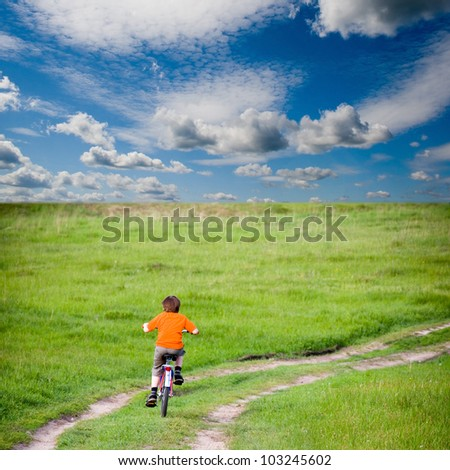 Boy rides a bicycle on a green meadow