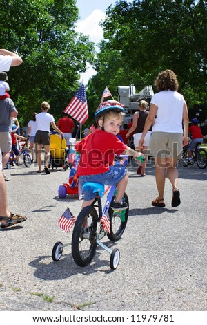 Boy riding his bike in a neighborhood 4th of July parade