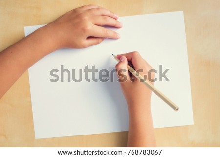 Boy right hand with pencil and left empty over a white blank sheet of paper lying on a wooden table. Top view, toned