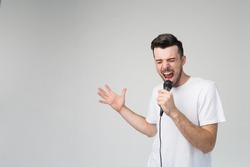 Boy Rocking Out. Image of a handsome man singing to the microphone, isolated on light. Emotional portrait of an attractive guy with a beard on a gray background