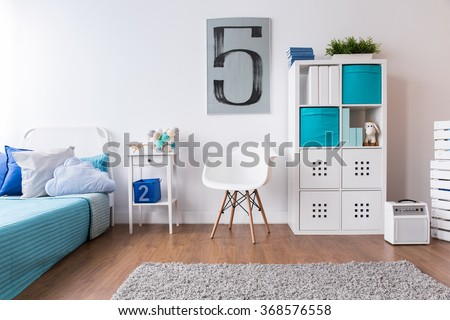 Boy room in white and blue with flooring and carpet