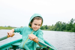 boy rowing a boat in the middle of the river. child enjoys boating