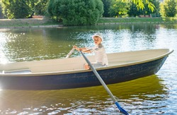 boy rowing a boat on a quiet river in. calm and relax. sun rays.