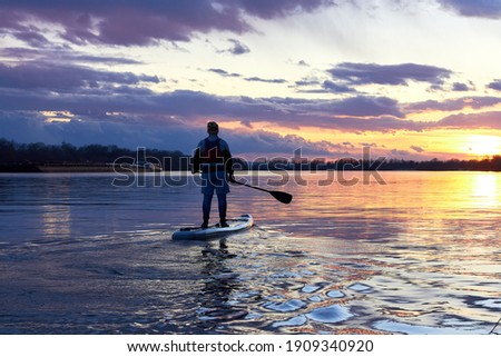 Boy rowing on stand up paddle boarding (SUP) paddling along the calm autumn Danube river against background of a colorful sunset. The concept of children's sports and tourism. Stock fotó ©