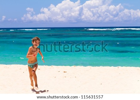 Boy running on a tropical beach with turquoise water