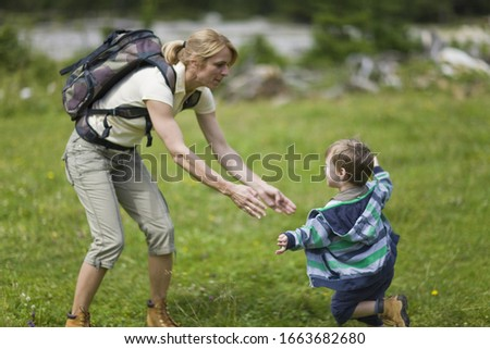 Boy running to his mother's arms in countryside
