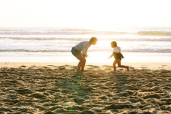 Boy running to his mother to hug her happily on a sunset at the beach