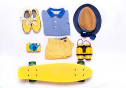 Boy's casual outfits - sneakers, striped shirt, hat, binoculars, sun glasses, camera, skateboard. Essential vacation items for traveler. Top view. Kids summer travel background. Flat lay clothes.