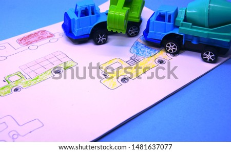 boy's drawing in drawing book and miniatures of excavator and concrete mixer truck