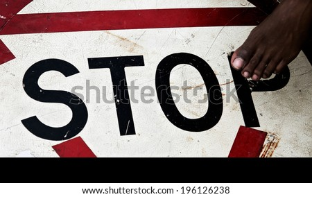 boy's foot about to step on an old stop sign