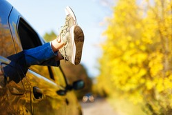 boy's legs in sneakers in the window car. boy in jeans lying on the backseat of the car with his legs crossed. feet shod in sneakers in the window against the sky, roads and bush with yellow flowers