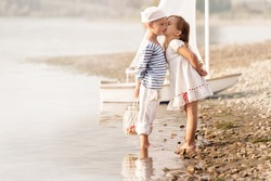 Boy-sailor with a girl walks around the lake on a summer day