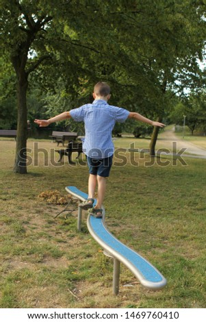 boy schoolboy in shorts walks on a horizontal sports game projectile on a playground in a park in summer, training coordination and body balance #1469760410