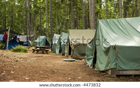 Boy scout campground. A typical campsite at a Boy Scout Camp includes tents, a table, dirt, and dirty clothes drying on a rope.