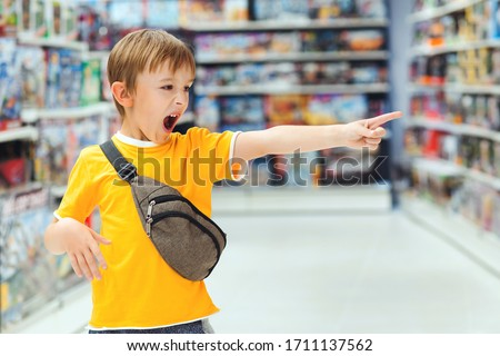 Boy screams and demands a toy in the store. Little boy getting hysterical in toy shop. ?hildren's tantrum in the store. Shop toys. Inside toy shop. Kid makes difficult choice in supermarket.