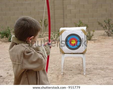 Boy shooting arrow at target - stock photo