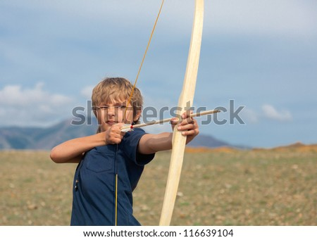 Boy shoots a bow at a target, in the open air