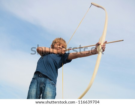 Boy shoots a bow at a target, in the open air - stock photo
