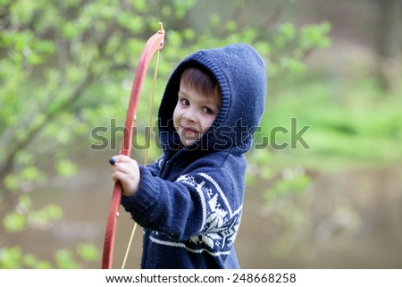 Boy shoots with bow at a target, in the open air