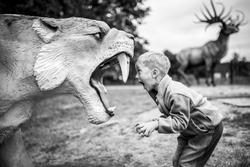 Boy shouting at the artificial saber-toothed tiger