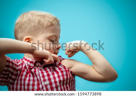 boy shows how strong he is. a strong child. physical activity in children