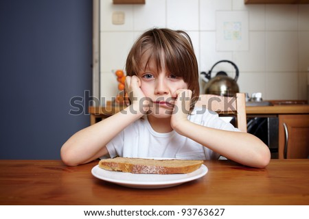Boy sits at kitchen table and refuse to eat his meal