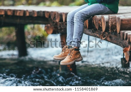 Boy sits on the wooden bridge over the river. Close up legs in boots image - Shutterstock ID 1158401869