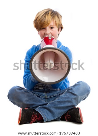 Boy sitting and shouting by a megaphone - stock photo