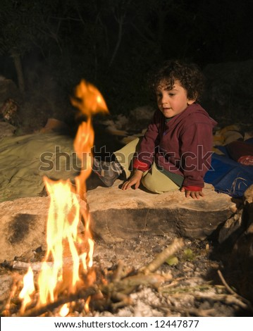boy sitting by the fire in a camp