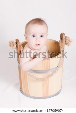 boy sitting in a wooden bucket