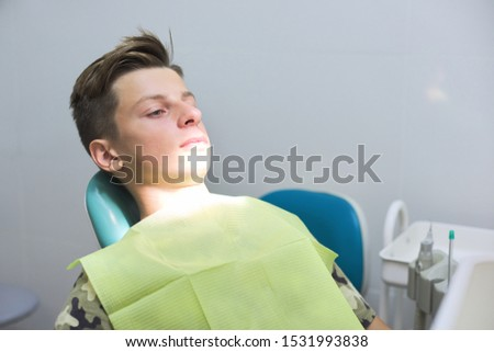 Boy sitting in dental chair at the clinic, teenager visits dentistry #1531993838