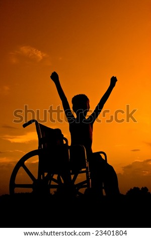 Boy sitting in wheel chair at sunset signaling victory