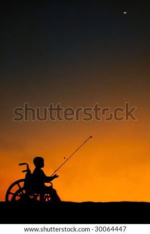 Boy sitting in wheel chair fishing at sunset