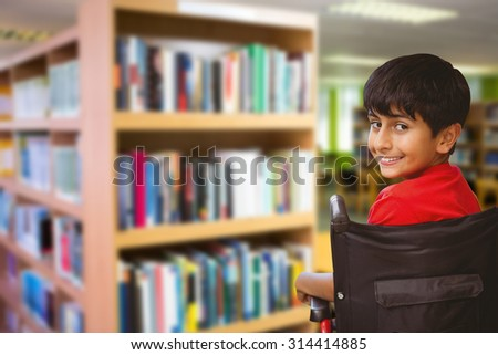 Boy sitting in wheelchair in school against volumes of books on bookshelf in library Volumes of books on bookshelf in library at the university