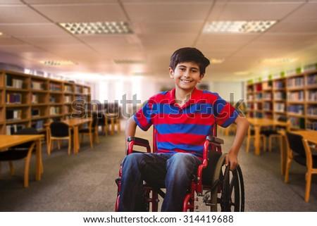 Boy sitting in wheelchair in school corridor against view of library