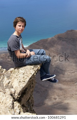 boy sitting on a rock with view to the canyon