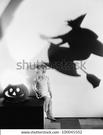 Boy sitting on a table with a pumpkin and a shadow of a witch on a wall - stock photo