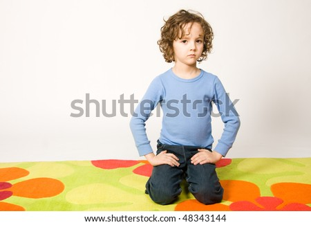 Boy sitting on colorful carpet