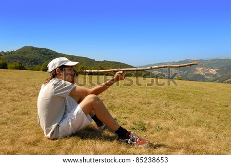 boy sitting on mountain meadow aiming with a stick as a gun